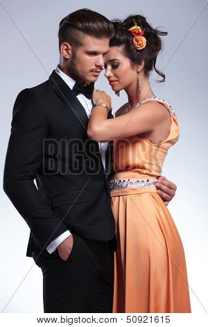 young fashion couple embracing romantically while the man holds his hand in his pocket and both looking away from the camera. on gray background