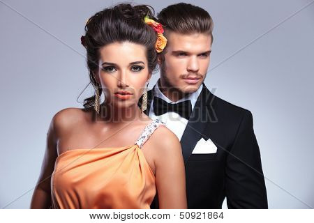 young fashion couple with man behind woman, looking away while she is looking into the camera. on gray background