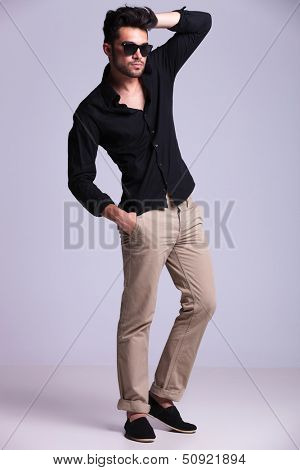 full length picture of a young fashion man standing with a hand in his hair and one in his pocket while looking away from the camera. isolated on a gray background