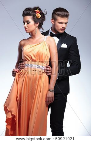 young fashion couple with man behind, looking in opposite directions, away from the camera. on gray background