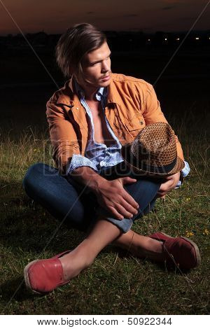 casual young man sitting outdoor with his hat on his knee and looking away from the camera