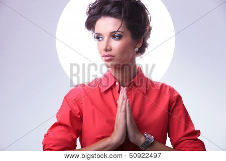 young casual woman praying with hands together and looking away while aura shines around her head. on gray background