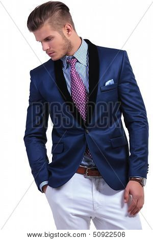 young business man looking down, to his side while holding a hand in his pocket. on a white background