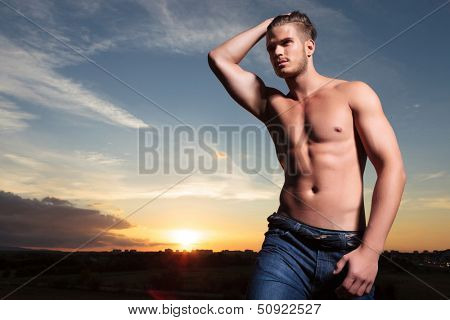 young topless man outdoor passing his hand through his hair while looking away from the camera with the sunset behind
