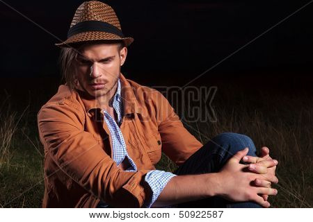 casual young man sitting outdoor in the grass and looking down while holding his knee with his hands, and a straw in his mouth