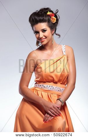 young fashion woman smiling and holding her hands together. on gray background