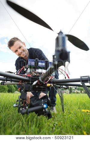 Portrait of young technician smiling while assembling camera on UAV drone in park