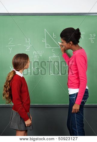 Side view of African American female teacher teaching mathematics to schoolgirl in classroom