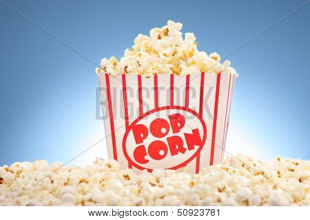 Popcorn in box overflowing with freshly popped corn against a blue background