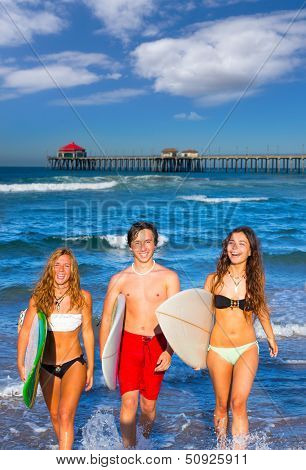 boys and girls teen surfers coming out from the Huntington beach California  [photo-illustration]