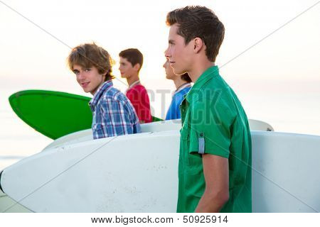 Surfer teenager boys group walking at beach shore on sunshine or sunset