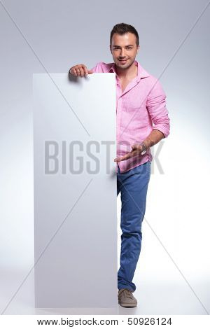 full length photo of a young casual man presenting a blank pannel while smiling for the camera. on gray background