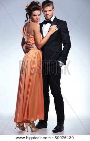 full length picture of a young fashion couple embracing and looking into the camera. on gray background