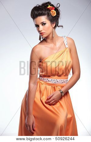 young fashion woman looks into the camera sensually. on gray background