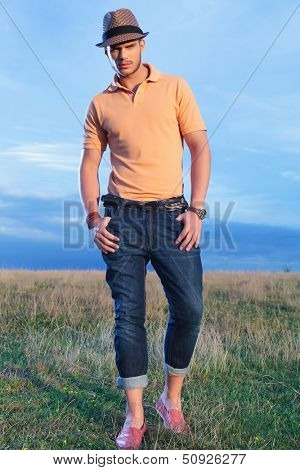 full length photo of a young casual man outdoor looking into the camera while holding both thumbs in his pockets