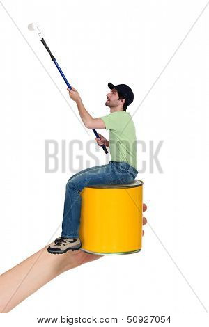 Man with a roller sitting on a can of paint