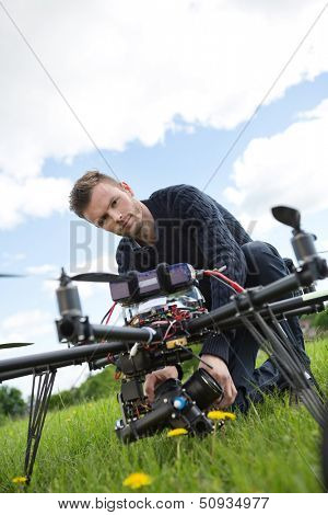 Portrait of young engineer fixing camera on UAV helicopter in park
