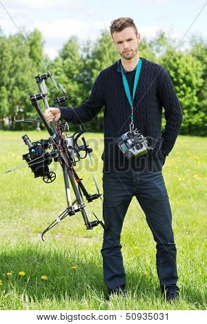 Portrait of young engineer standing with UAV drone and remote control in park
