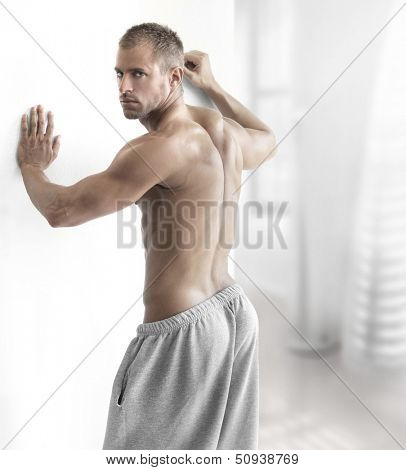 Sexy portrait of a muscular man shirtless in modern setting