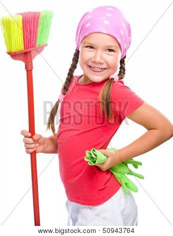 Young girl is posing as a cleaning maid and holding broom, isolated over white
