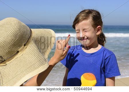 Mother applying sunscreen on child on the beach