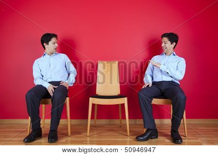 two businessman looking each other with a suspicion look, next to a red wall