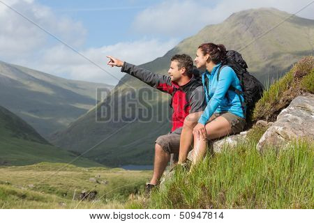 Couple taking a break after hiking uphill with man pointing in the countryside