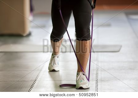 exercising with a resistance band, close up of female legs