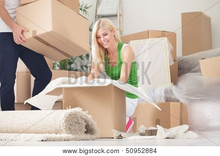 Happy young woman unpacking boxes in new home