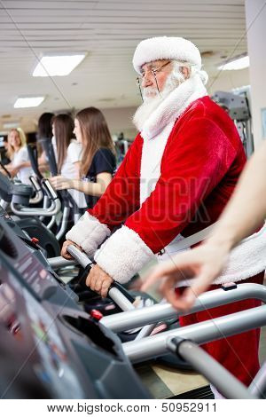 Santa Claus workout  on a treadmill at gym