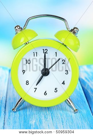 Alarm clock on table on blue background