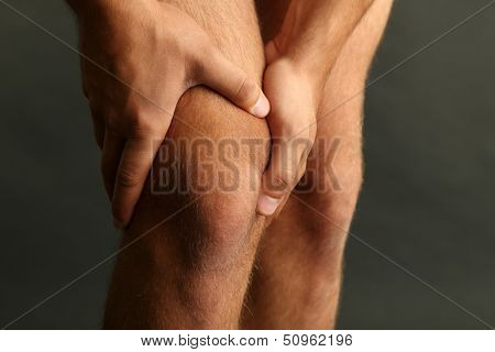 Young man with knee pain on dark background