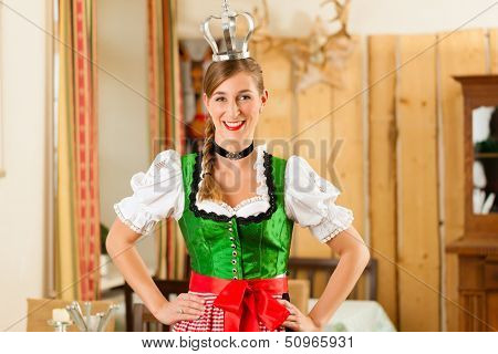 Young woman as queen in Traditional Bavarian Tracht in restaurant or pub
