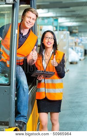 Logistics Teamwork - forklift driver, Worker or warehouseman and his coworker with tablet computer at warehouse of freight forwarding company