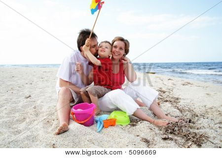 Young Happy Family On The Beach