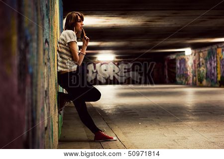 Stylish young girl standing in grunge graffiti tunnel, shanty town. Fashion, trends, subculture. Full body shot