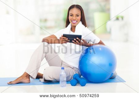 cheerful african woman holding tablet computer after exercise