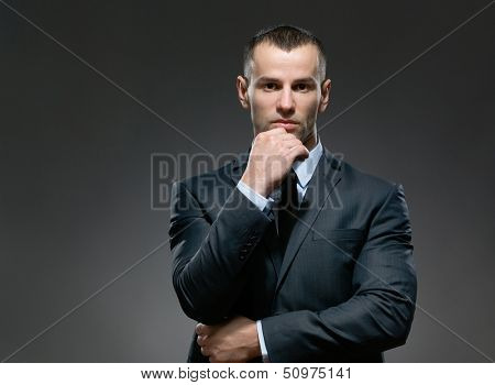 Pensive and self-confident businessman props head with hand