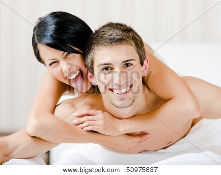 Close up of laughing couple who plays in bedroom. Woman lying on the back of the man embraces him
