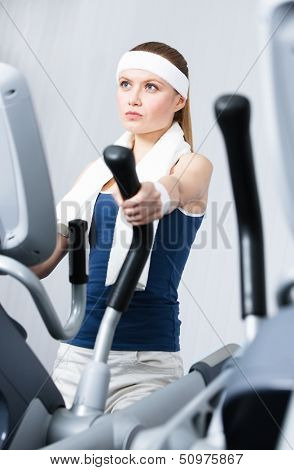 Young athlete woman training on simulators in gym
