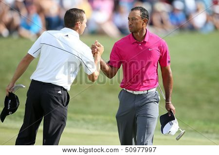 Sep 15, 2013; Lake Forest, IL, USA; Tiger Woods (r) shakes hands with Sergio Garcia on the 18th green after the third round of the BMW Championship at Conway Farms Golf Club.