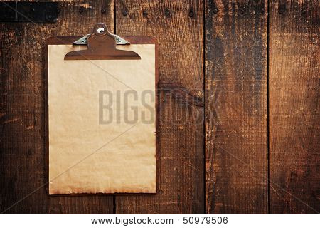 Old clipboard on grungy wooden surface, with plenty of copy space.