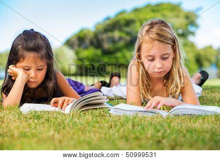 Cute Little Girls Reading Books Outside on Grass after School