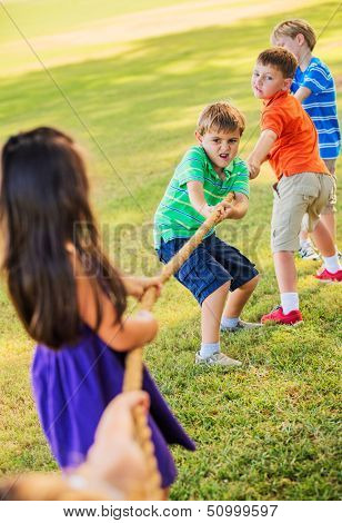 Group of Kids Playing Tug of War On Grass