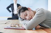 stock photo of boredom  - Young businesswoman sleeping during meeting - JPG