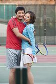 Couple embracing next to the tennis net