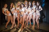 Eight beautiful showgirls posing on stage, focus on the girl in the center. poster