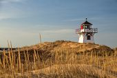 stock photo of dune grass  - Lighthouse nestled in the sand dunes at Dalvay - JPG