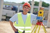 picture of theodolite  - Portrait of builder worker with theodolite transit equipment at construction site outdoors during surveyor work - JPG