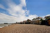 pic of herne bay beach  - Pebble beach with a row of small huts with a pier stretching out to sea in the background - JPG